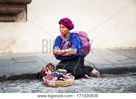 ANTIGUA, GUATEMALA-DEC 26, 2015: : Old guatamalian woman salling traditional goods at the street in Antigua, on Dec 26, 2015, Guatemala.