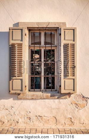 Window with shutters with old wall on sunset in Tel Aviv, Israel.