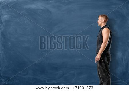 Muscular young man is standing and looking forward on blue chalkboard background. Sport and healthy lifestyle. Keep fit. Athletic body