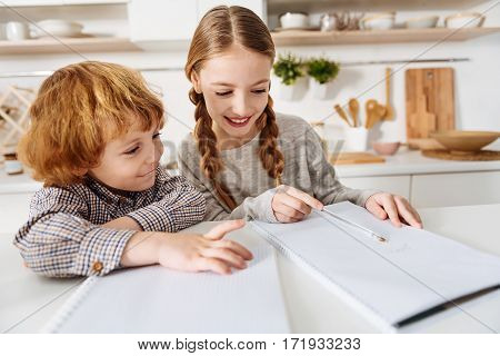 Learning new things. Intelligent determined cute lady being a tutor for her sibling while they both spending time in the kitchen and working on their home assignment