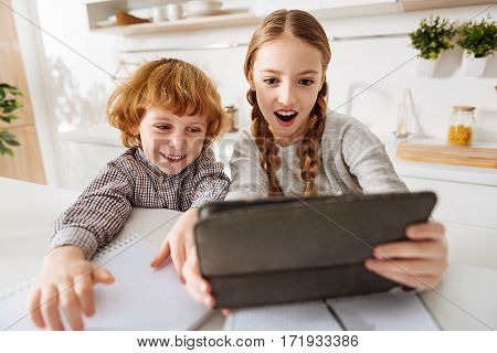 Two of us. Beautiful cheerful young girl using her gadget making a photo of herself and her brother while taking a break during studying