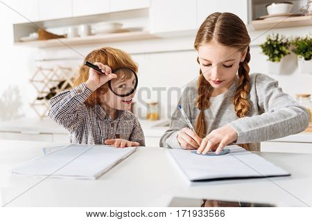 Have a little fun. Hilarious active ginger boy playing with a magnifying glass while his sister trying doing her home assignment for math class