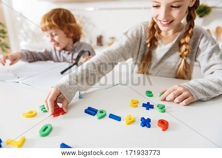 Understandable colors. Clever caring positive girl teaching her cute ginger brother some arithmetic while using a special colorful numbers and arranging them in appropriate order