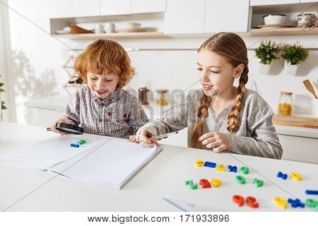 Loving math. Hard working intelligent young lady doing her math assignment writing down the formulas while her little brother being fascinated with a set of colorful numbers
