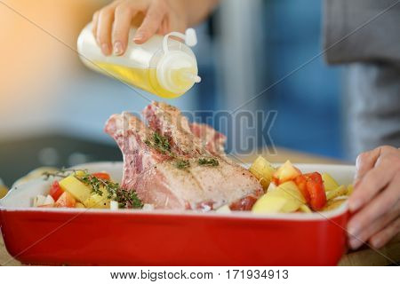 Closeup of woman spreading olive oil on meat dish
