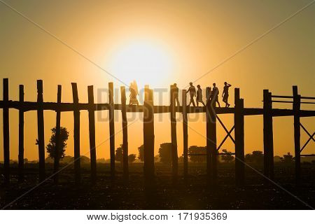 Silhouettes of people walking on the U bein bridge at sunset. Amarapura, Myanmar