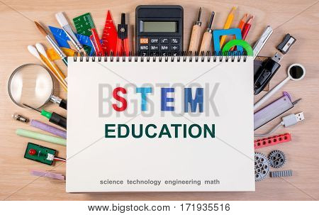 Stem Education Text On Notebook Over School Supplies Or Office Supplies On School Table. Background