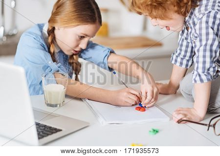 Both science and art. Brilliant curious pretty girl drawing mathematical calculation using special colorful plastic figures trying explaining basic calculation rules to her little brother