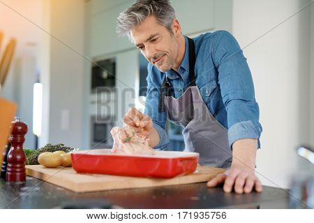 Mature man in kitchen cooking dish for dinner