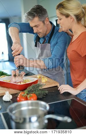 Middle-aged couple having fun cooking together in home kitchen