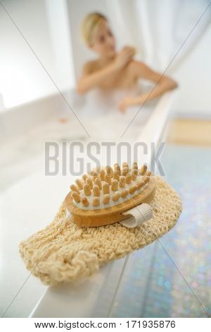 Closeup of massage gloves set on bathtub