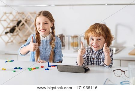 Having fun with benefits. Beautiful clever energetic children expressing their positive altitude by holding their thumbs up and looking pretty joyous