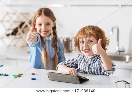 Easy and educative. Enthusiastic motivated bright siblings looking pretty satisfied after solving math riddles while playing special educative games together