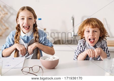 Little rabbits. Amusing positive artistic siblings doing funny faces imitating bunnies while sitting at the table in a roomy sunlit kitchen