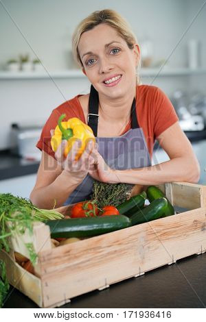 Portrait of smiling blond woman in kitchen cooking for dinner