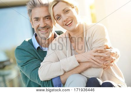 Cheerful middle-aged couple sitting in front of new home
