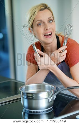 Portrait of woman in kitchen ready to cook pastry