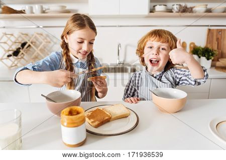 Liking her cooking. Sweet caring pretty girl making her little brother a sandwich with peanut butter while they both sitting at the table and her sibling looking excited