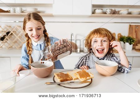 Chocolate fuel. Positive charming adorable siblings having a plentiful nutritious breakfast consisting of peanut butter sandwiches and cereal before going to school