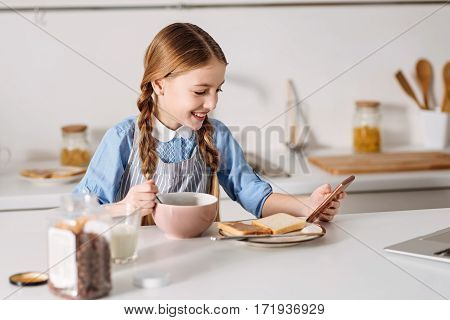 Scrolling down the page. Nice clever elegant child having a nutritious morning meal while using her gadget looking through some new articles