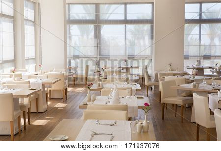 Empty hall of the restaurant with tables ready for the lunch