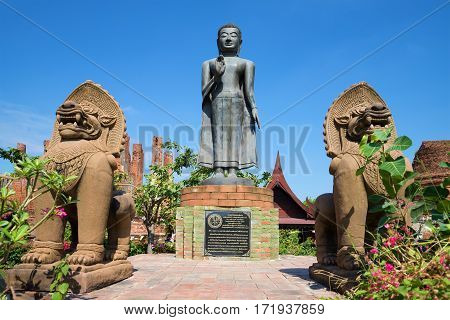 AYUTTHAYA, THAILAND - JANUARY 01, 2017: View of a sculpture of standing Buddha on a sunny day. Wat Thammikarat in the historic town