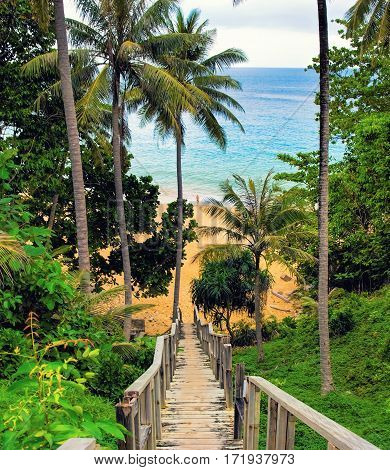 Old wooden down stairs to the beach with palms around. Naithon beach Phuket Thailand