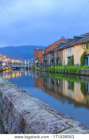 Otaru Japan historic canal and warehouse in summer twilight time people are walking alongside the canal famous tourist attraction of Sapporo Hokkaido.