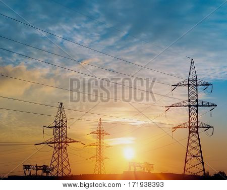 Silhouette of high voltage electrical pole. Sunset sky background