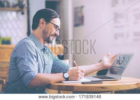 Plan everything in time. Positive cafe owner sitting at the table and solving money issues while expressing positivity