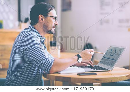 Is everything correct. Pleasant responsible cafe owner sitting at the table and using laptop while managing his little business