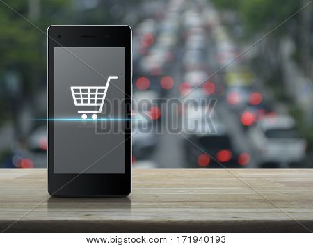 Shopping cart icon on modern smart phone screen on wooden table over blur of rush hour with cars and road Shop online concept