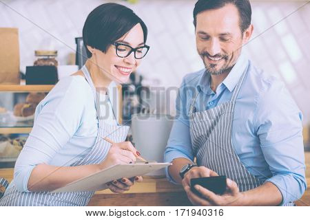 Make all the calculations. Positive delighted couple of cafe owners making calculations and biscussing money matters while standing near counter