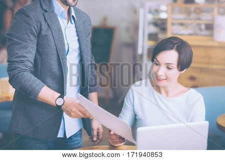 Important papers. Pleasant adult woman sitting at the table and workign in the cafe while her collegue giving her documents