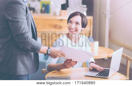 Thank you. Cheerful smiling adult woman sitting at the table and getting papers from her collegue while feeling content