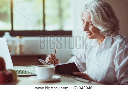 Put it down. Cheerful delighted aged woman sitting in the kitchen and making notes while expressing gladness