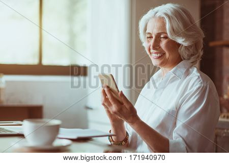 Nice morning. Cheerful delighted aged woman using cell phone and resting in the kitchen while expressing joy