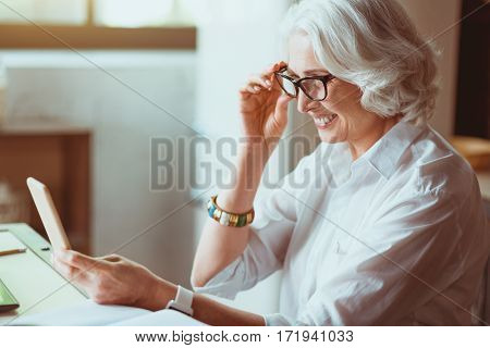 Modern world. Joyful smiling aged woman using smart phone and smiling while sitting in the kitchen