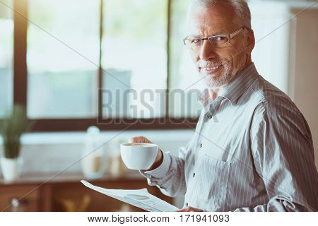 Source of energy. Positive smiling aged man holding papers and drinking coffee while standing in the kitchen