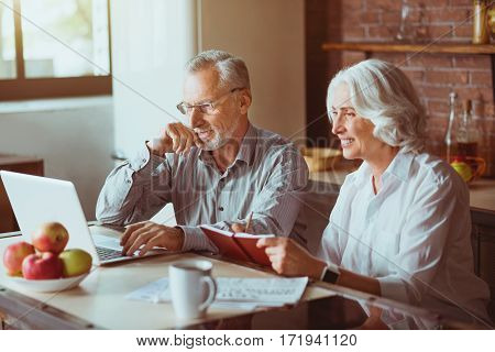 Involved in modern world. Cheerful smiling aged couple sitting in the kitchen and expressing gladness while using laptop