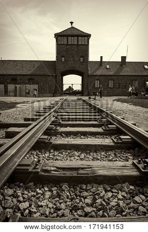 OSWIECIM POLAND - AUG 18: Main gate and railroad to concentration camp of Auschwitz Birkenau on August 18 2015 in Oswiecim Poland.