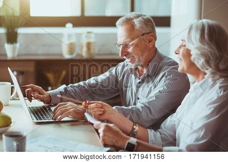 Have a look. Cheerful aged smiling couple expressing gladness and using laptop while sitting in the kitchen