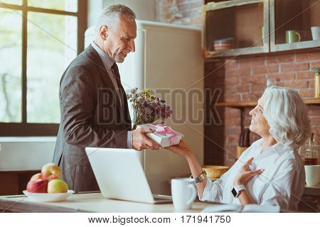 For you. Pleasant smiling aged woman sitting in the kitchen while her loving husband presenting her flowers