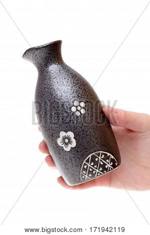 Hand holding sake bottle isolated on white background