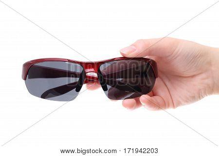 Hand holding black sun-glasses isolated on white background