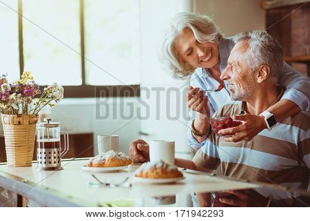 Try it. Cheerful aged couple having breakfast together while loving woman giving raspberry to her husband in the kitchen