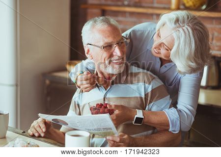 Try it. Cheerful delighted aged woman giving raspberry to her husband while he is reading newspaper
