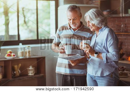 Every day press. Cheerful content aged couple drinking tea and reading newspaper while standing in the kitchen