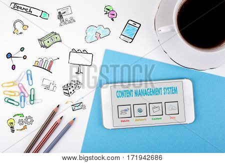 Content Management System concept. Mobile phone and coffee cup on a white office desk.