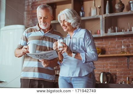 Be informed. Positive delighted aged couple reading newspaper and driking tea while standing in the kitchen